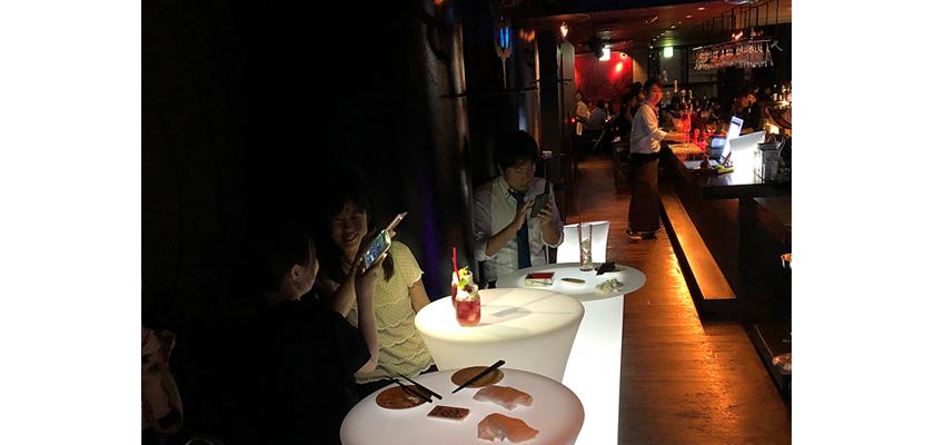 光るLED内蔵家具クラシオン。テーブルの前でSNSに投稿する女性客。福岡市中央区春吉のバー&ダイニングミツバチの店内画像